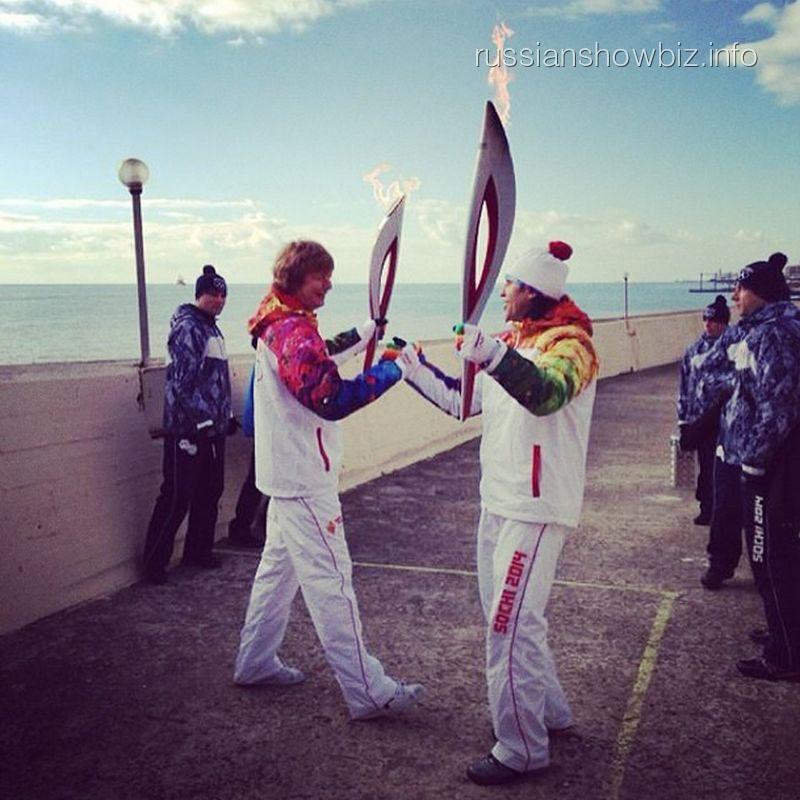 Андрей Григорьев Аполлонов принимает олимпийский огонь от Александра Реввы