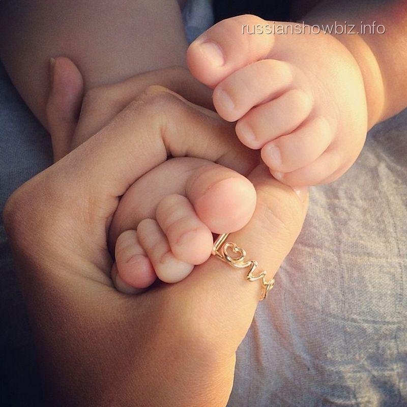 Ольга Шелест держит ножки дочки